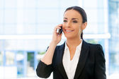 Woman in formalwear talking on mobile phone — Stock Photo