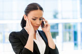 Frustrated woman in formalwear talking on phone — Stock Photo