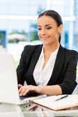 Woman in formalwear working on laptop — Stock Photo