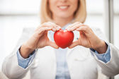 Female doctor  holding heart — Stock Photo