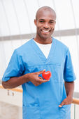 African doctor holding heart prop — Stock Photo