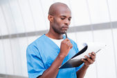 African doctor holding clipboard — Stock Photo