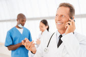 Cheerful doctor on the phone. — Stock Photo