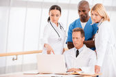 Doctors discussing and looking at laptop — Stock Photo