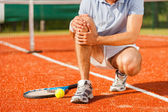 Tennis player touching his knee — Stock Photo
