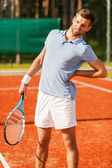 Tennis player touching his back and grimacing — Стоковое фото