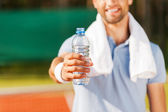 Man stretching out bottle with water — Stock Photo