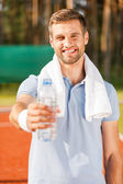Young man stretching out bottle with water — Stock Photo