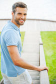 Handsome young man moving downstairs — Stock Photo