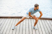 Young man doing stretching exercises — Stock Photo