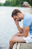 Depressed man at riverbank — Stock Photo