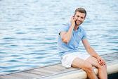Homem sorridente, falando no telefone celular — Foto Stock