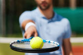 Man holding tennis ball on his racket — Stock Photo