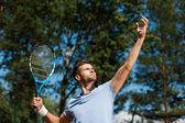 Уверенно мужской теннисный игрок выступающей мяч — Стоковое фото