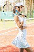 Sonriente mujer sosteniendo la raqueta de tenis — Foto de Stock