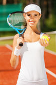 Smiling woman holding tennis racket — Stock Photo
