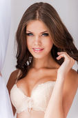Beautiful woman in bra touching her hair — Stock Photo
