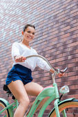 Young smiling woman riding bicycle — Stock Photo