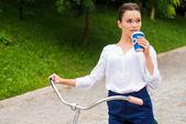 Giovane donna con una bicicletta nel parco — Foto Stock
