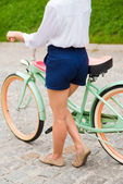 Young woman walking with bicycle — Stock Photo