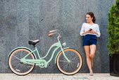 Young woman standing near bicycle — Stock Photo