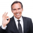 Smiling businessman while gesturing OK sign — Stock Photo #50425007