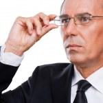 Thoughtful mature businessman adjusting eyeglasses — Stock Photo #50425475