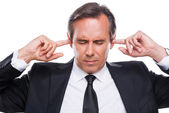 Confident mature businessman holding fingers in ears — Stock Photo