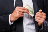 Businessmen hiding money to his pocket — Stock Photo