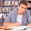 Confident young man making research in library — Stock Photo