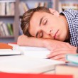 Handsome young man sleeping in library — Stock Photo #50630663