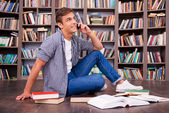 Happy young man sitting against bookshelf — Stock Photo