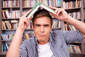 Frustrated man carrying book on head — Stock Photo