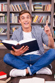Young man holding book and gesturing — Stock Photo