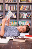 Happy young man reading book — Stock Photo