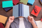 Young man covering his face with books — Stock Photo
