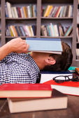 Young man covering his face with book — Stock Photo