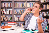 Happy young man talking on mobile phone — Stock Photo