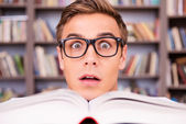Surprised young man looking out of book — Stock Photo