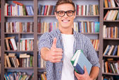 Young man holding books and showing thumb up — Stock Photo