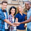 Happy young people holding their hands together — Stock Photo