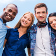 Four happy young people looking at camera — Stock Photo #50655229