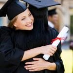 Happy women in graduation gowns hugging — Stock Photo #50655825