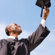 Man in graduation gown holding mortar — Stock Photo #50656481