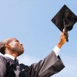 Man in graduation gown holding mortar — Stock Photo #50656511