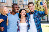 Four happy young people making selfie — Stockfoto