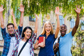 Happy young students with raised hands — Stock Photo
