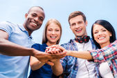 Four happy young people bonding and holding hands — Stockfoto