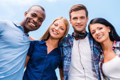 Four happy young people looking at camera — Stockfoto