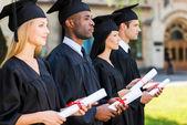 College graduates holding their diplomas — Foto Stock